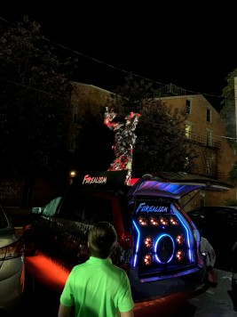 Shiny man dancing on a car